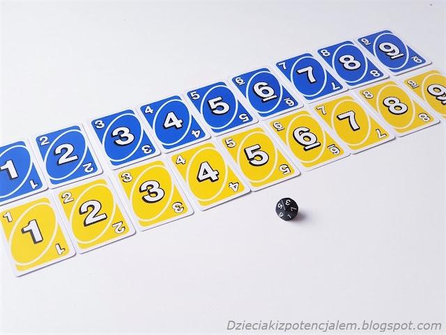 Karty Uno w kolorach niebieskim i żółtym ułożone w dwóch rzędach od wartości 1 do 9 oraz kostka dziesięciościenna w kolorze czarnym