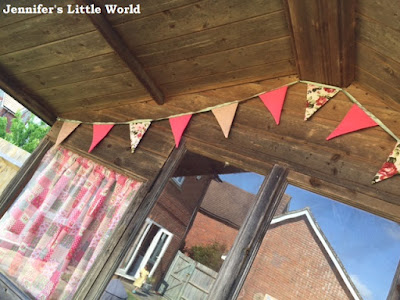 Scruffy summerhouse with bunting outside