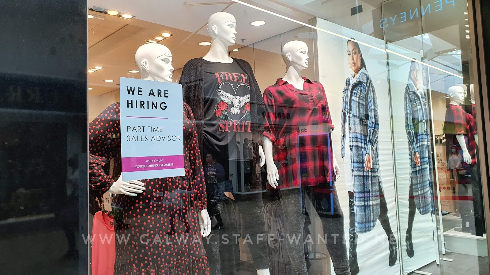 Shop window with printed transfer 'we are hiring' sign - models wearing a red print dotted dress, red plaid oversided shirt, Free Spirit tee-shirt with a stylized eagle, and a poster of a blue and white plaid fabric winter coat