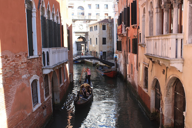 Some people in a Gondola in a Venice canal.