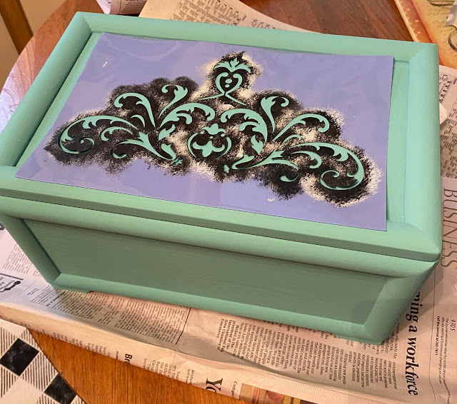 Photo of a jewelry box painted turquoise with scrolly stencil on top