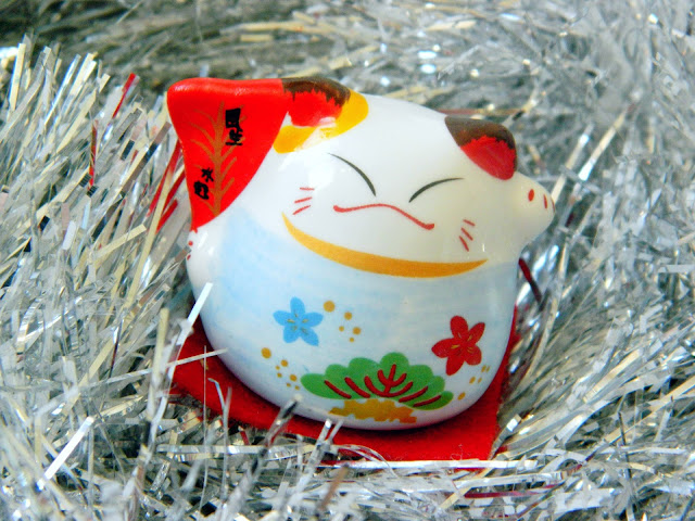 A photo of a maneki neko or japanese/chinese lucky cat ornament, sitting on silver tinsel.