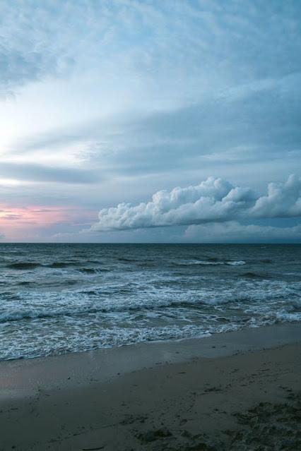 imagen de la orilla del mar atardeciendo con nubes de tormenta