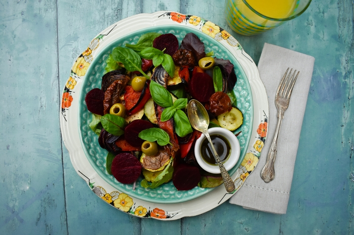 Close up of A substantial winter salad filled with roast vegetables on a bed of salad leaves, with sundried tomatoes, pickled beetroot, olives and a pesto balsamic dressing. Suitable for vegetarians and vegans.