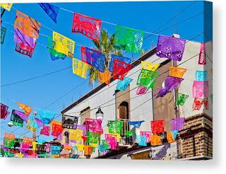 Color Papel Picado strung from a white building under a bright blue sky. By Bernard Borcas.