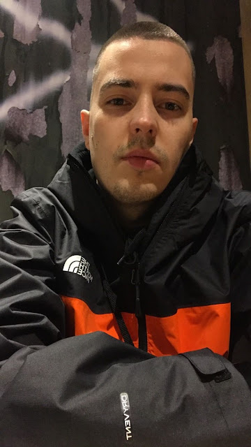 Pictured is Norwegian producer and DJ, Shokk. Wearing a red and orange jacket.
