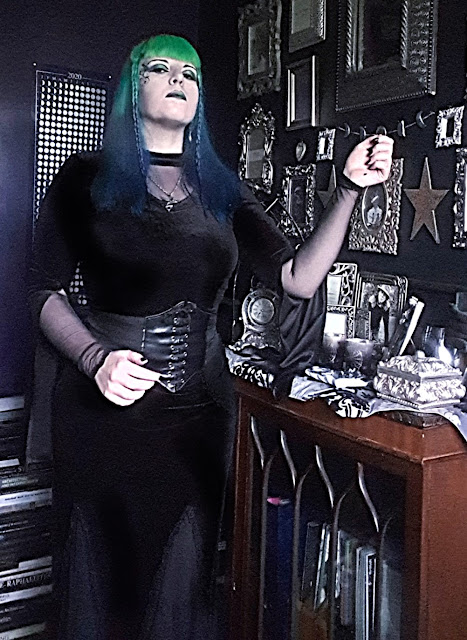 A Gothic woman standing. Behind her is a dark purple wall with a poster of the phases of the moon/moon calendar for 2020. To her left is a black wall with an assortment of ornate silver frames, and a dark-brown wooden cabinet with  glass front of several Gothic arches, on top of which is a silver and black damask table-runner and many ornate silver-coloured items. Behind her to the right is a stack of books on art, architecture and archaeology. She is wearing a close-fitting black velvet top with a v-neck mesh insert at the neck; the sleeves of the blouse have the outer velvet layer split from the wrist to the elbow so the droop down and reveal a mesh inner sleeve. She has an hourglass figure achieved with a corset. She is wearing a faux-lether waist-cincher over her clothes; it laces up at the front, but this is a false closure. She is wearing a black velvet skirt that is close fitting at the top, but flares at the bottom. It has mesh insert panels at the bottom and a 'hankerchief' hem