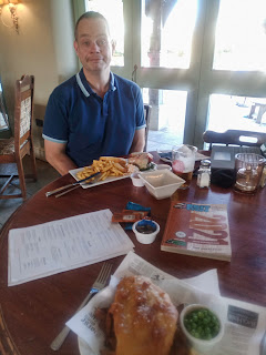 Photo of Neil sitting at an indoor dining table which has the BritStops book on it. There are also two meals: a burger meal and a fish and chips meal.