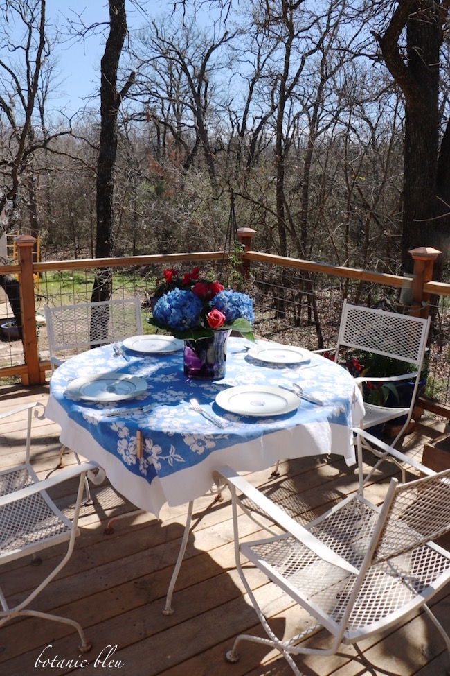 blue-white-dogwood-tablecloth-round-wrought-iron-table-on-deck