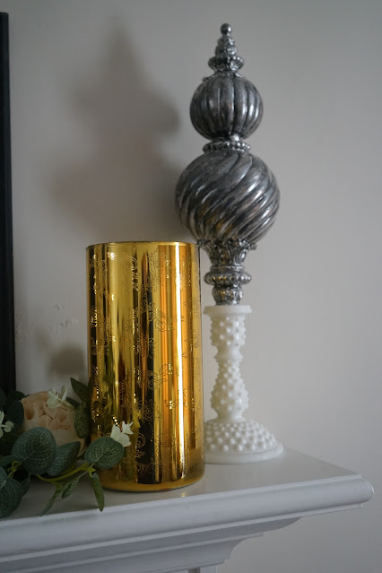 Gold hurricane and milk glass hobnail candlestick on mantel