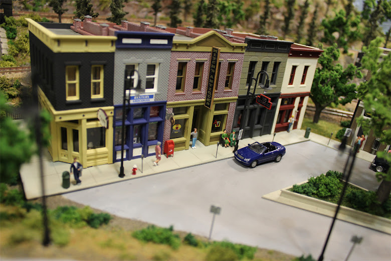 Sidewalk scene in front of a Merchant's Row 1 kit including figures, meters, benches, fire hydrants and vehicles