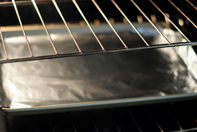 A foil-lined baking sheet in the oven.