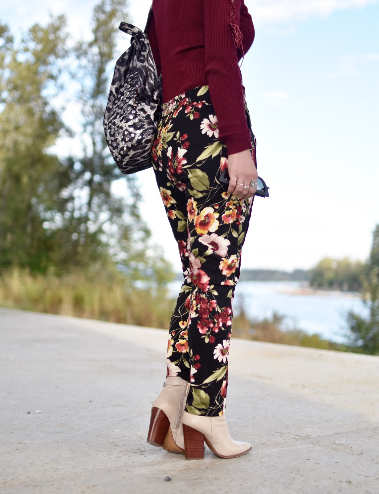 Monika Faulkner outfit inspiration - maroon sweater, floral trousers, ivory booties, leopard-patterned backpack