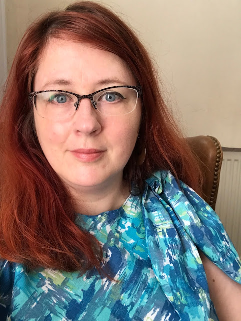 The head and shoulders of a redheaded woman in a top that ties at one shoulder. The top is in various shade of blue, plus a splash of spring green.