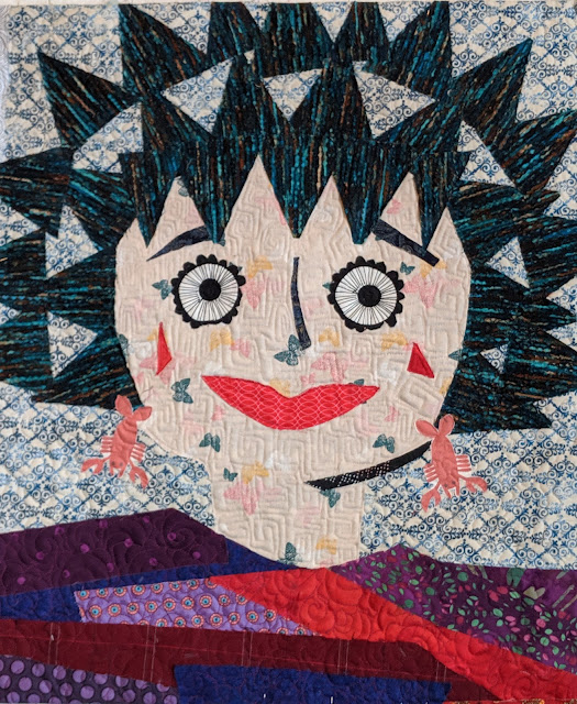 Collage quilt of a smiling face with large eyes, spiky hair, and lobster earrings. The binding is faced.
