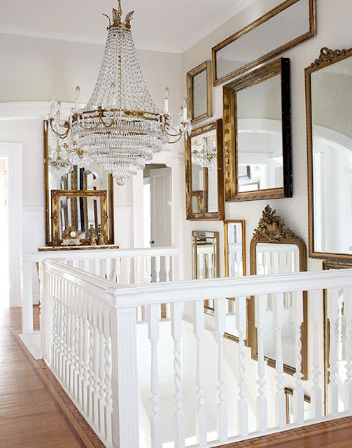 white upstairs landing with gallery of vintage mirrors in interior designer Annie Brahler of Eurotrash