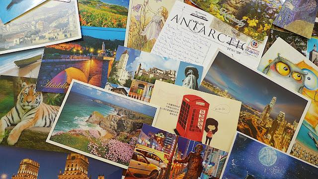 Viele Postkarten auf einem bunten Haufen. Mit Tiger, englischer Küste, Zeichnungen, Städte bei Nacht und sogar eine Postkarte aus der Anarktis