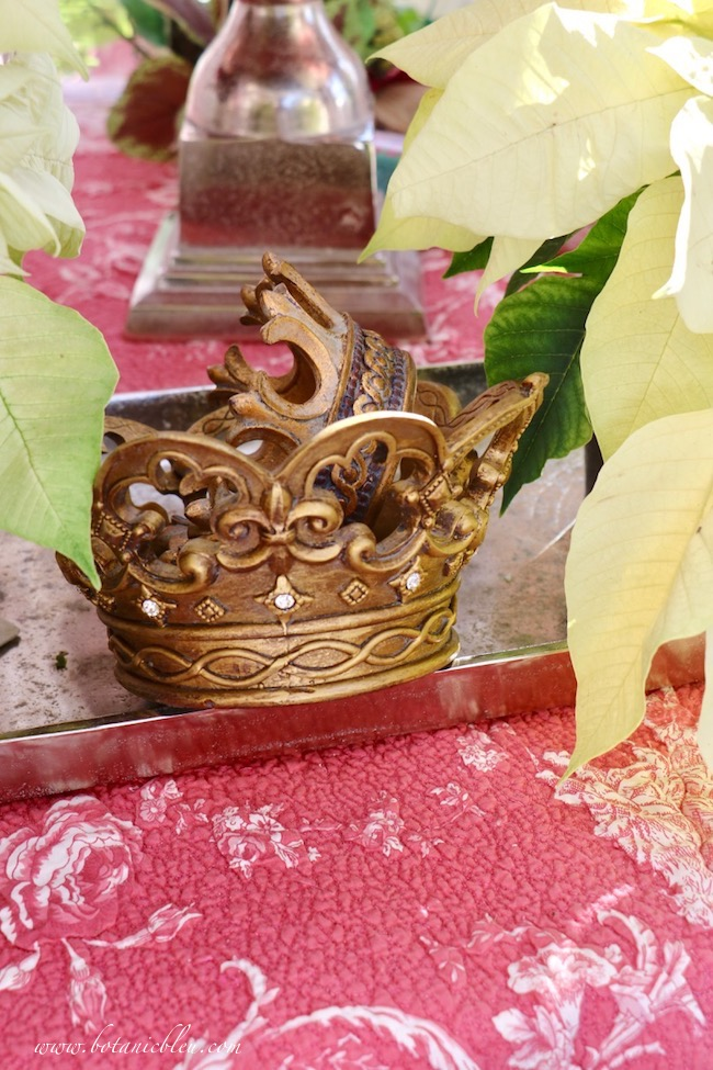 Gold crowns with fleur de lis designs nestle between white poinsettias in the French Country Christmas greenhouse