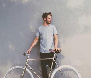 Young man standing by a bicycle