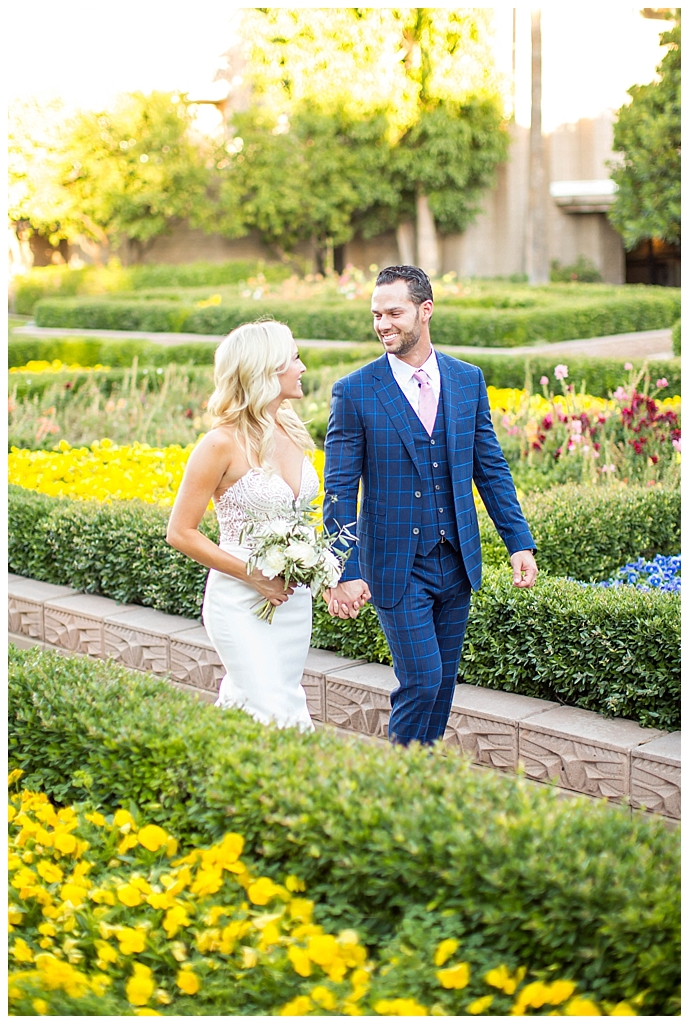 bride in two piece wedding dress and groom in custom blue suit in the garden at Arizona Biltmore