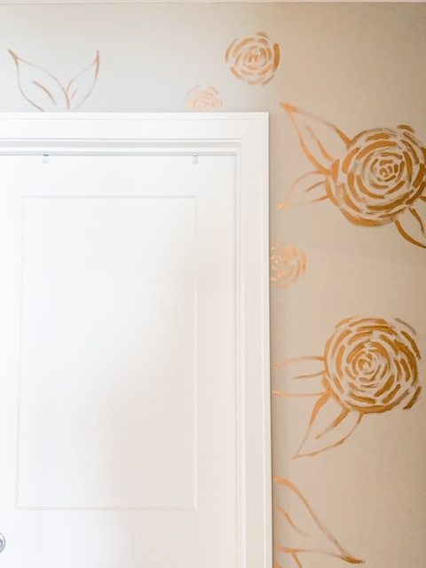 gold painted flowers on the bathroom wall