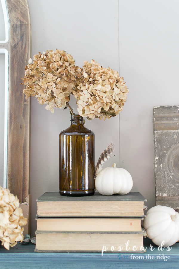 brown bottle with dried hydrangeas and small white pumpkin on fireplace mantel