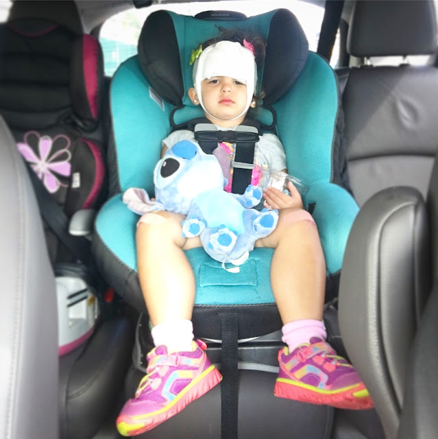 Toddler girl with bandages wrapped around her head frowns while sitting in her carseat