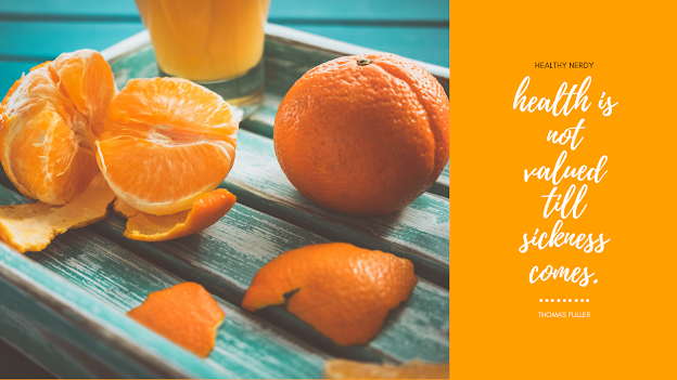 Orange coloured background with oranges and their pieces kept on a wooden tray.