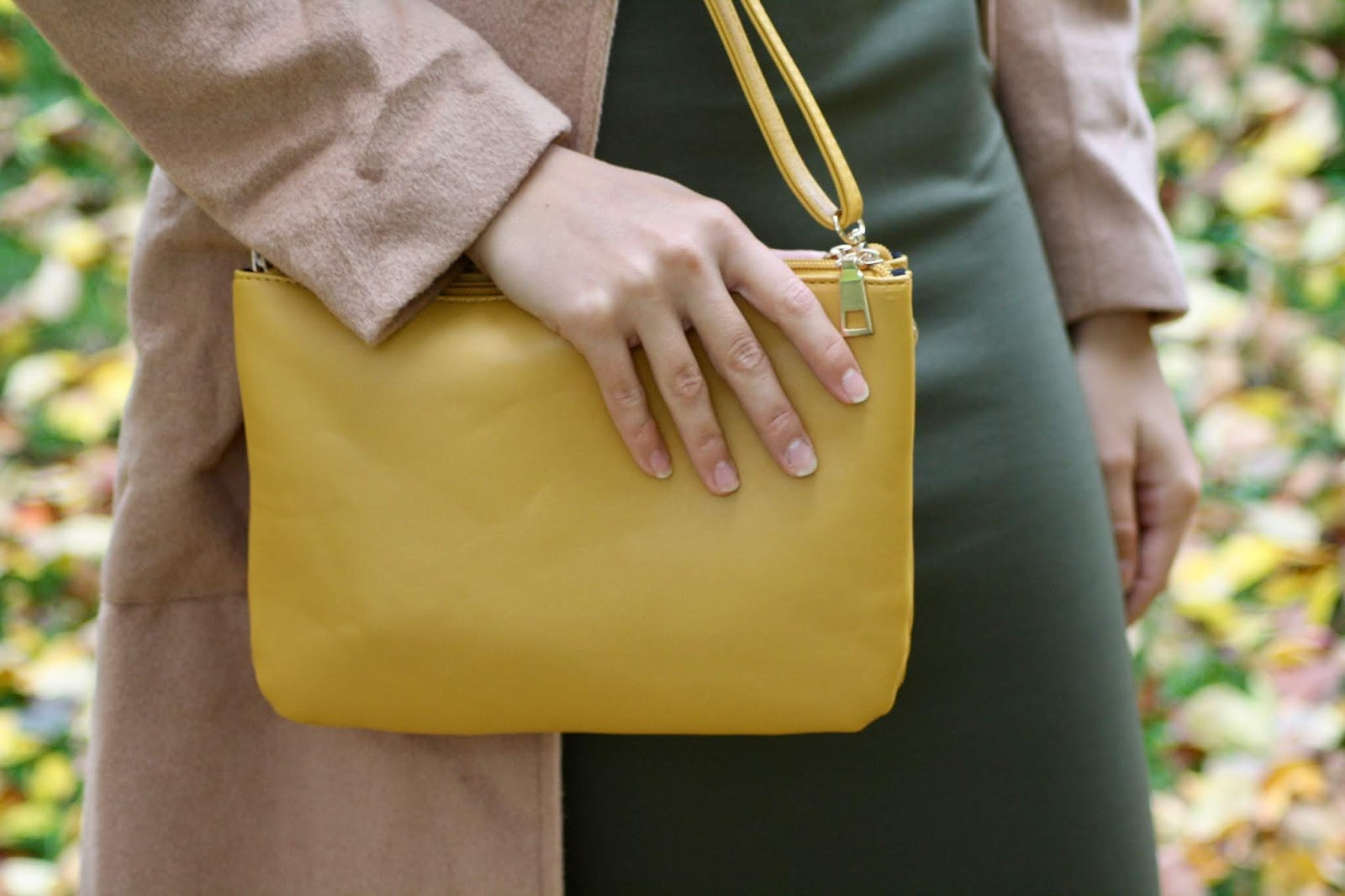 close up of woman holding mustard handbag, autumn leaves in background