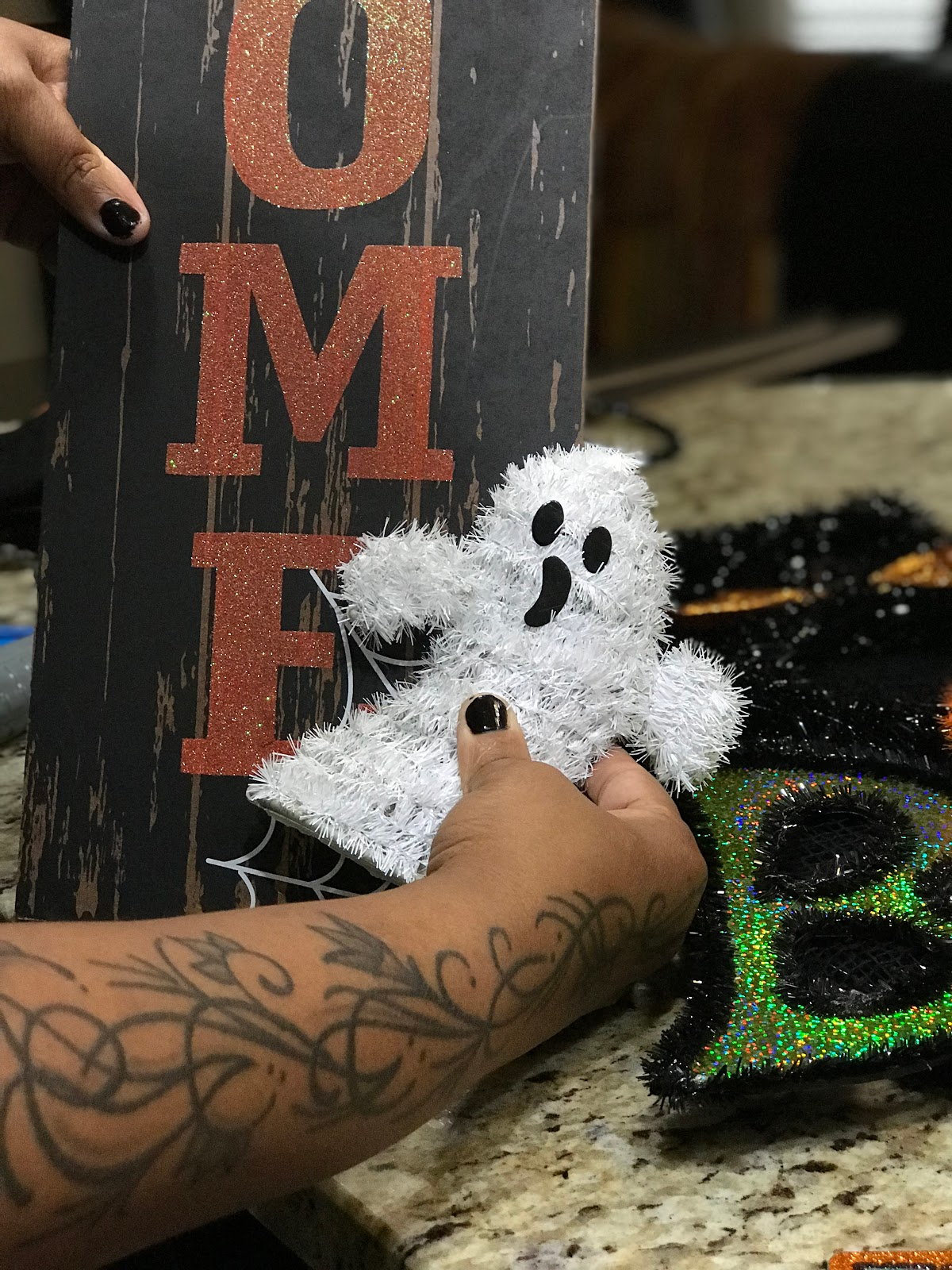 Image: Ghost being glued onto Halloween sign for decor