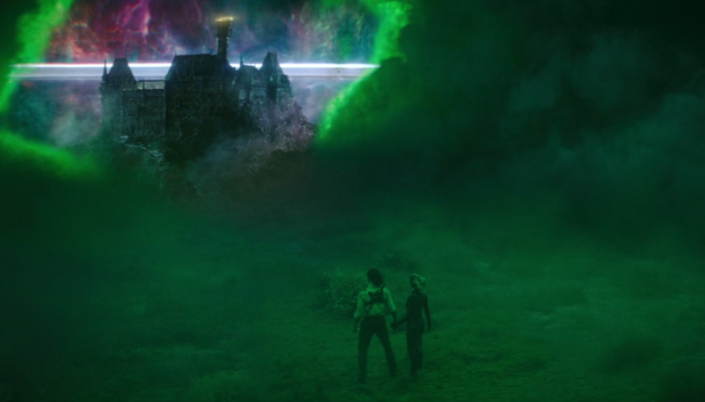 Imagem: Loki e Sylvie estão num lugar com névoa verde ao redor desistam de costas e olhando para uma abertura no céu feita com uma aresta quadrada de brilho e para fora da abertura dá para ver uma grande mansão preta em um estilo sombrio.