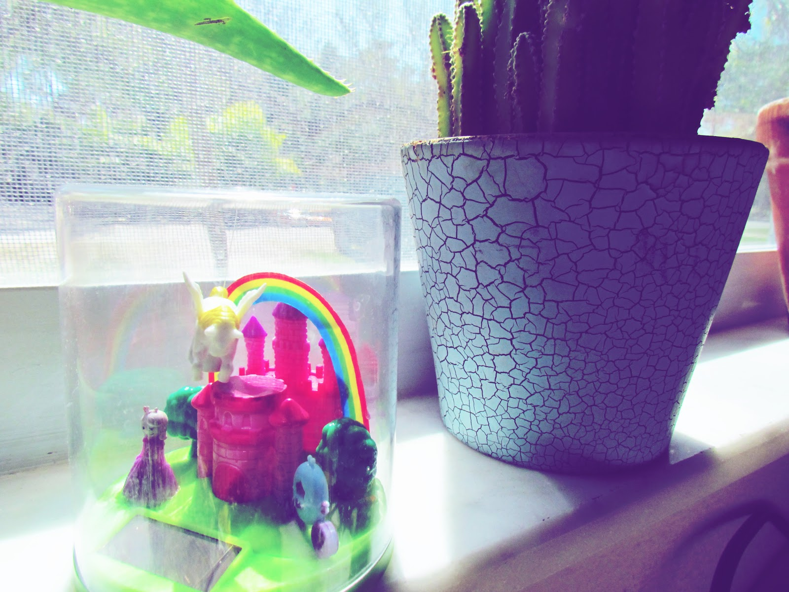 A crackled paint blue pottery with a plant and a tiny biosphere with a castle, a princess doll, and a magical unicorn and rainbow in the sky