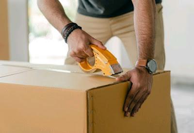 A man taping a cardboard box shut.