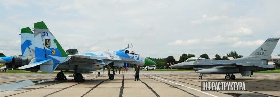 на фото літаки Су-27 831-ї бригади та F-16C Block 30H, 100th Fighter Squadron, 187th Fighter Wing на миргородському аеродромі, 2011 рік