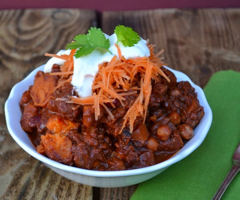 A bowl of sweet potato and puy lentil mole (chilli) topped with grated carrots and sour cream