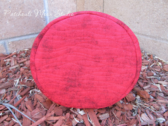 Bottom of fabric bucket showing quilting on red fabric