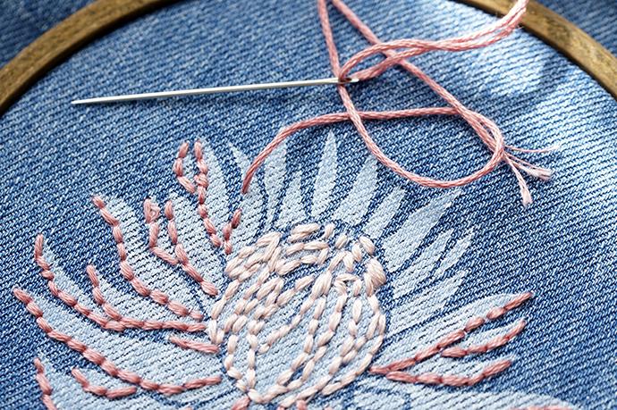 Gedrucktes Motiv auf Jeansstoff mit rosa Garn umsticken