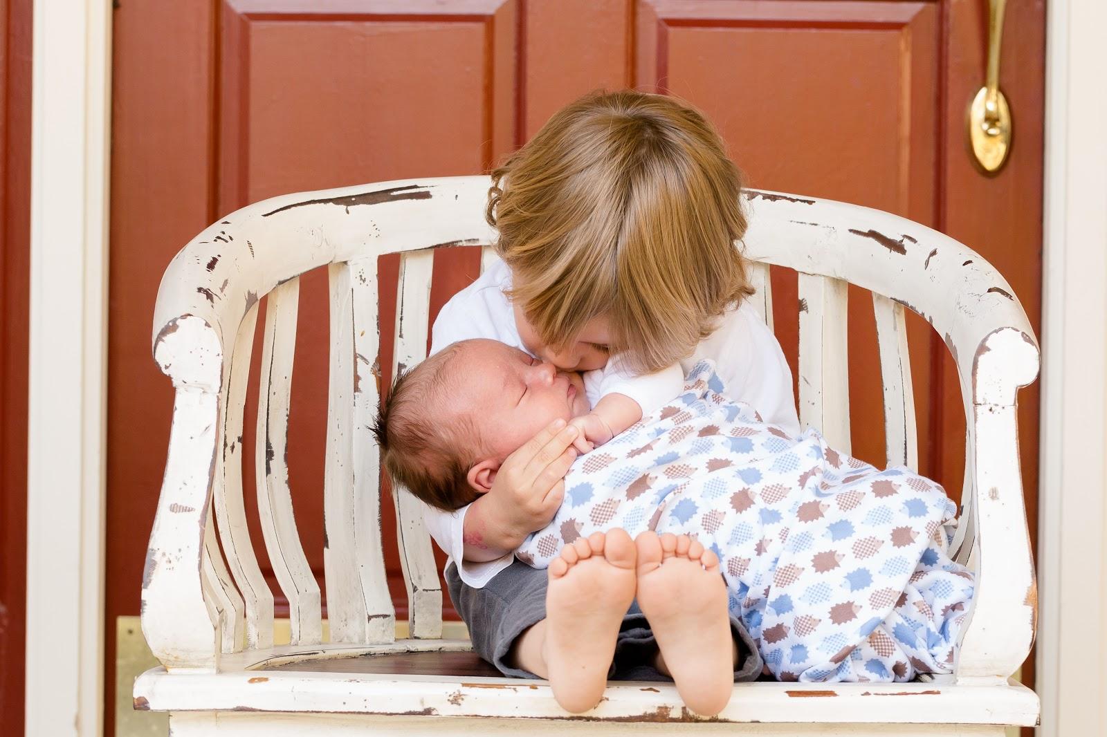 新生児の弟を抱っこして顔を近付ける少年の兄