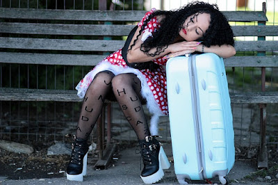 Girl Sleeping on a Park Bench, Head Resting on Her Suitcase