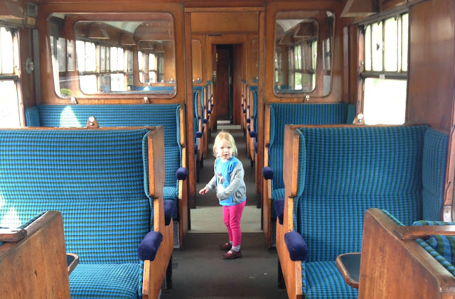 A toddler in an old fashioned train carriage with wooden seats on Epping Ongar railway