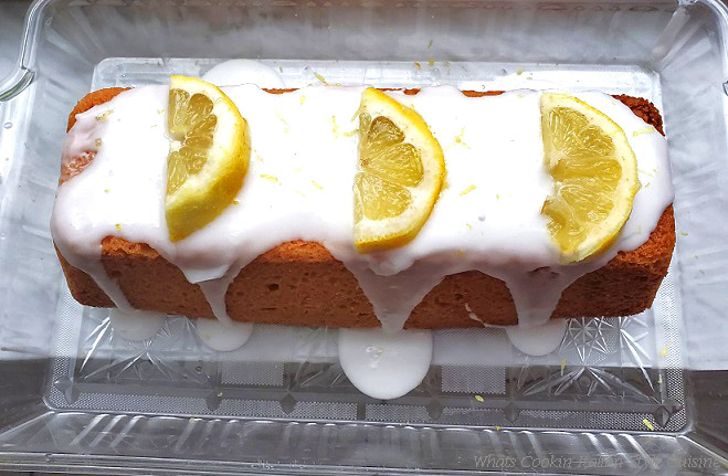 This is a lemon loaf cake baked with a thick drizzle of white frosting and fresh lemon slices on top. The cake is long and on a plastic pretty decorative tray to serve it on.