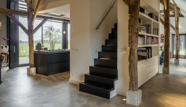 Staircase and concrete flooring in dramatic barn conversion house
