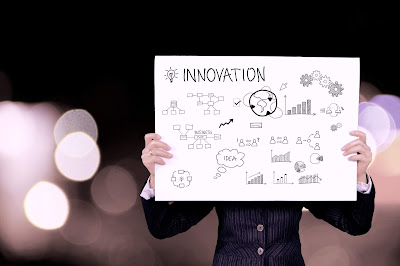 photo of person holding sign with word 'innovation' and various doodles