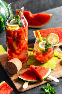 2 fruit-filled glasses of pinkish liquid sitting on a cutting board surrounded by pieces of watermelon.