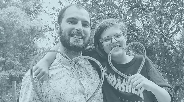 Foto com filtro cinza azulado, mostrando pai e filho segurando corações de madeira e sorrindo.