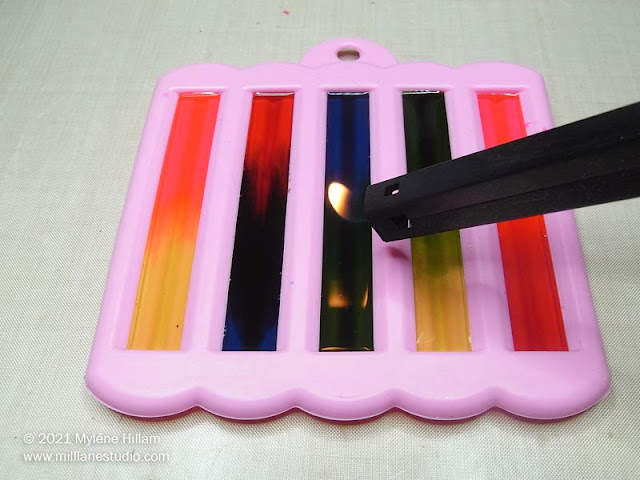 Using a long-neck lighter to pop bubbles in multi-coloured resin bars
