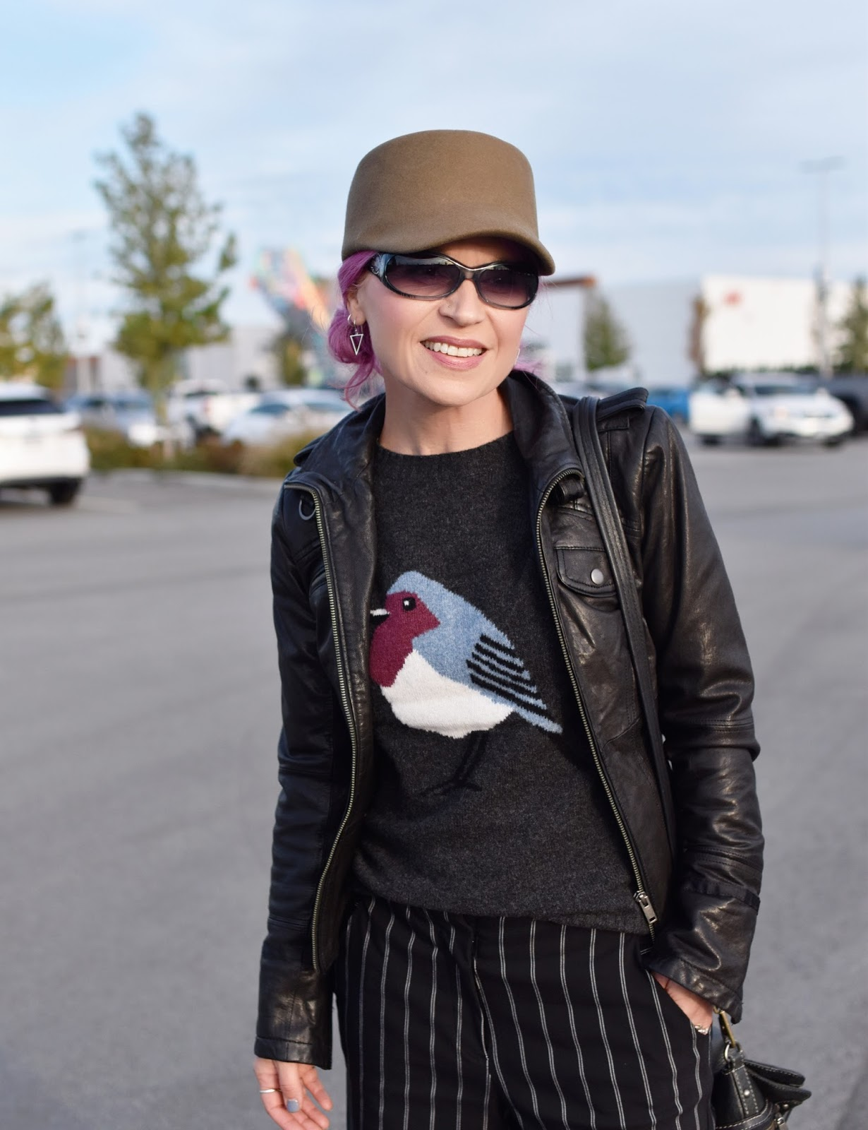 Monika Faulkner outfit inspiration - bird-motif sweater, moto jacket, military-inspired cap