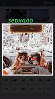 две кружки в руках и зеркало заднего вида в машине
