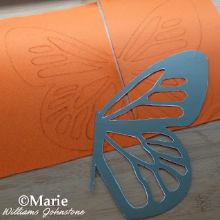 Orange felt sheets with traced butterfly design