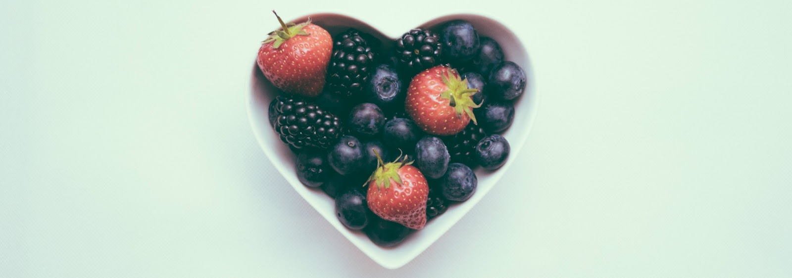 heart-shaped-bowl-of-fruit-on-white-background